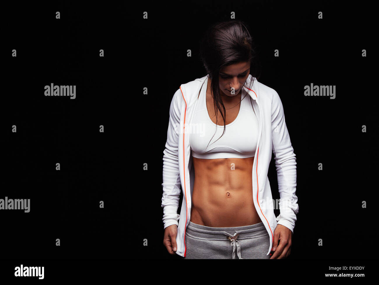 Portrait of a fit young woman with perfect abdomen muscles in sportswear. Muscular female athlete looking down on - Stock Image