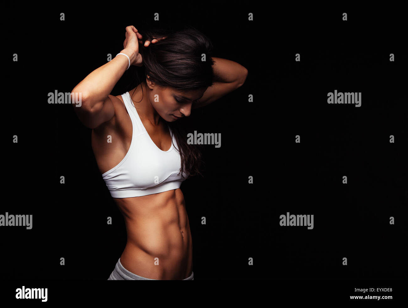 Studio portrait of a young woman getting ready for exercising on black background. Sporty young woman tying her - Stock Image