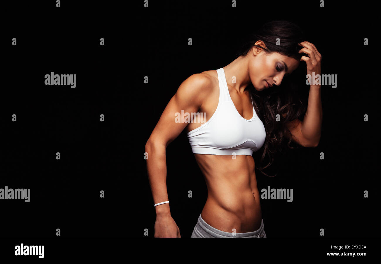 Image of young woman in sports wear thinking while standing against black background. Thoughtful fitness model. - Stock Image