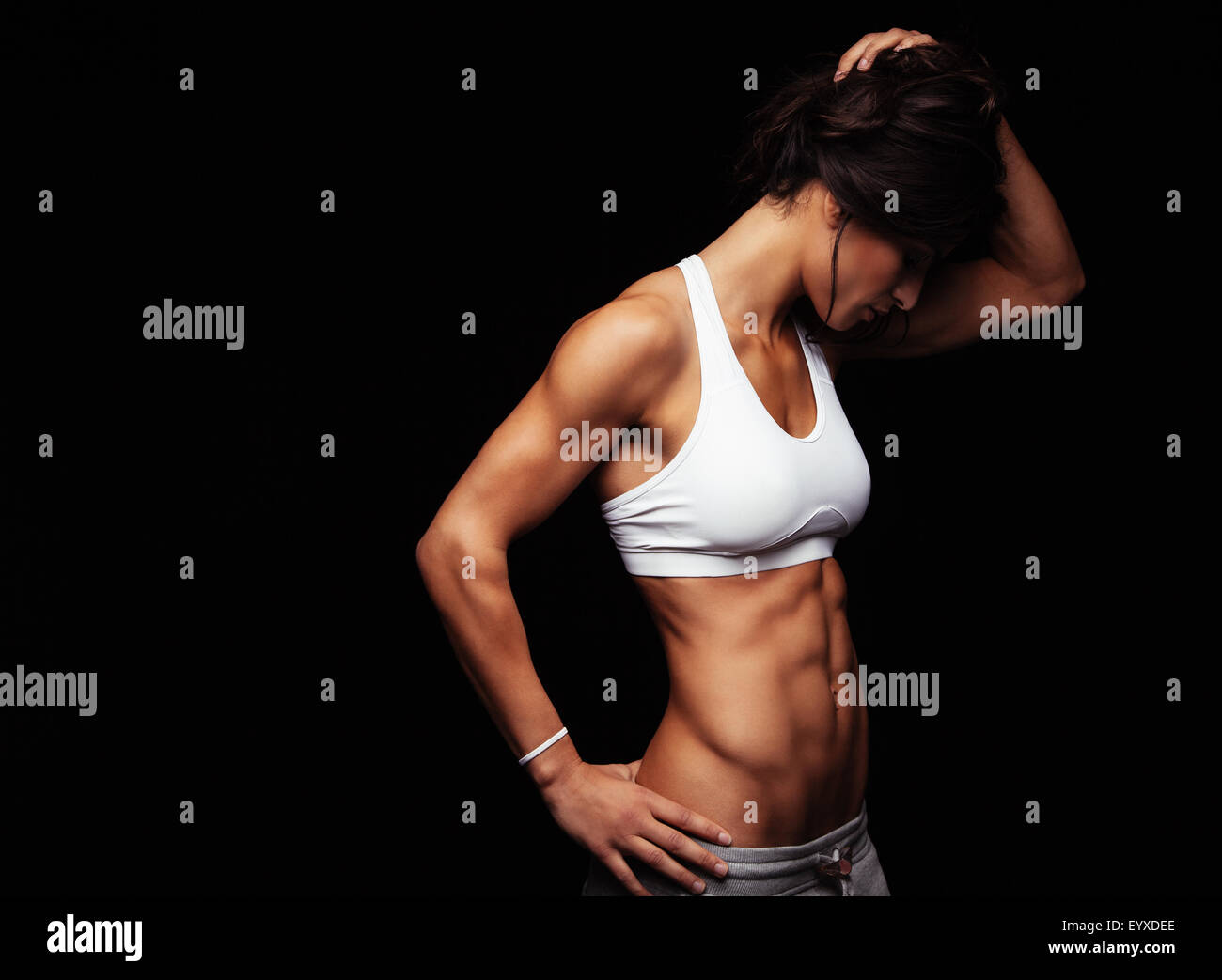 Image of fit young woman in sports wear looking down while standing on black background. Muscular fitness model Stock Photo