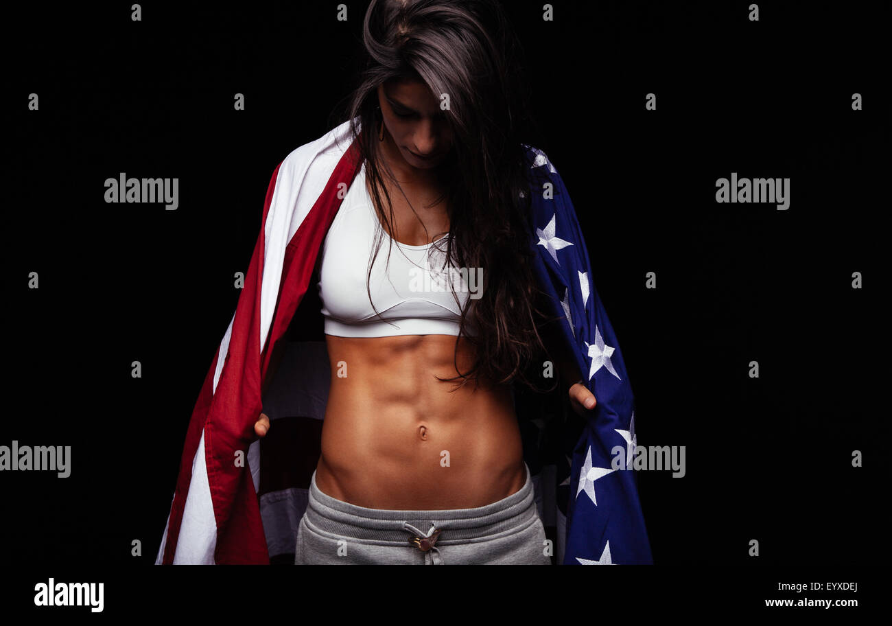Female athlete carrying an American flag against black background. Studio shot of muscular sportswoman with USA - Stock Image
