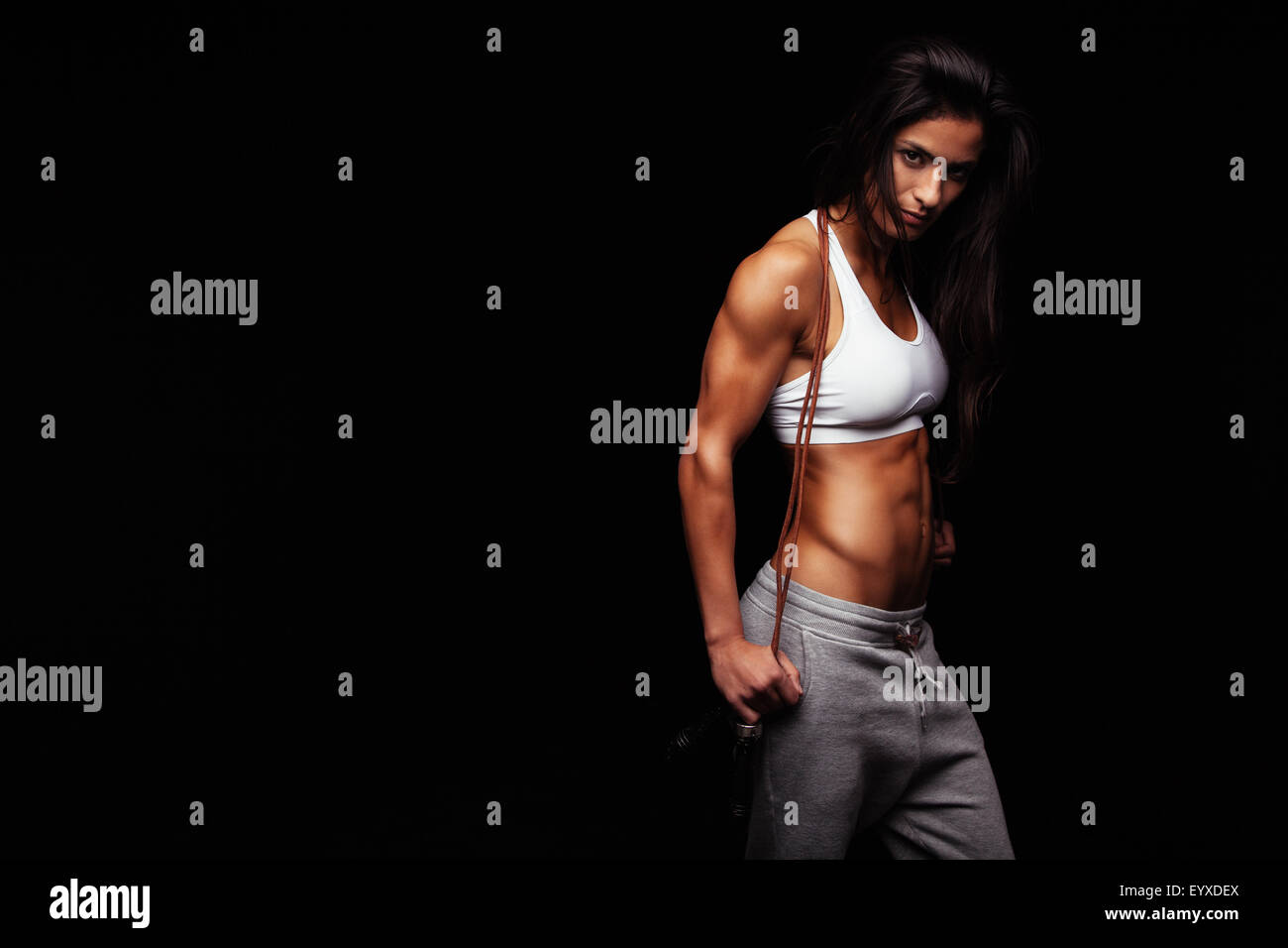 Confident young female athlete posing with jumping rope looking at camera. Muscular woman with skipping rope standing - Stock Image