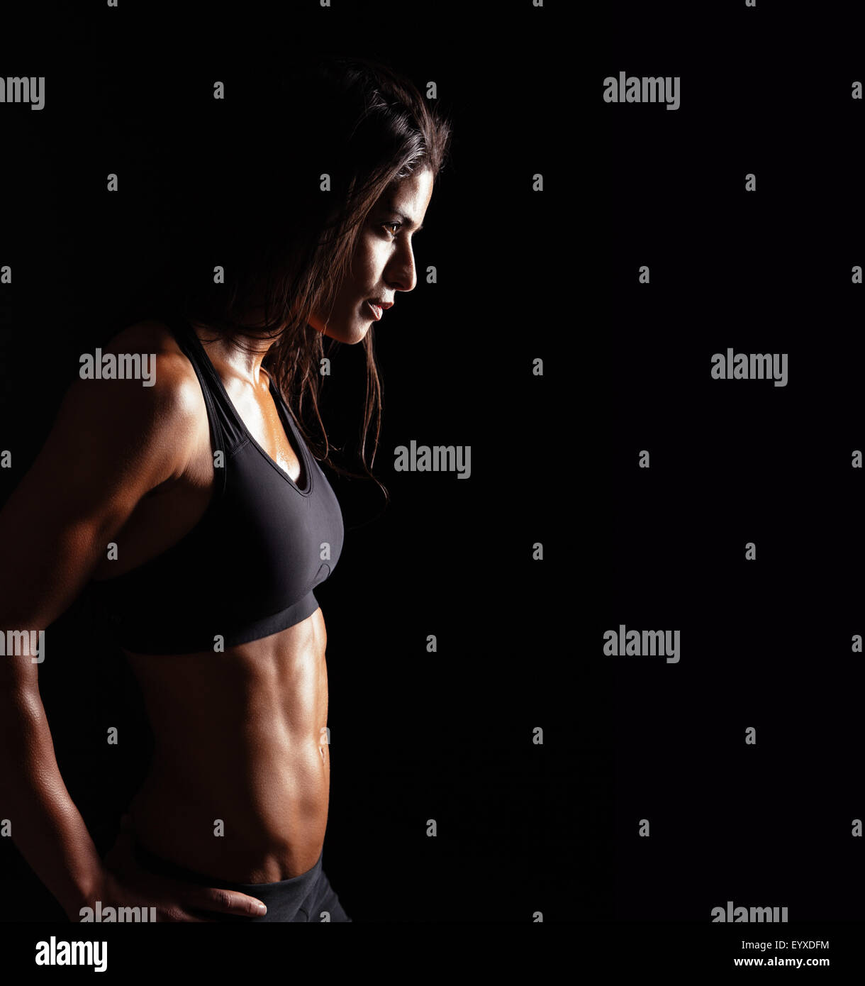 Image of fitness woman in sports clothing looking away on black background. Young female with perfect muscular body. - Stock Image