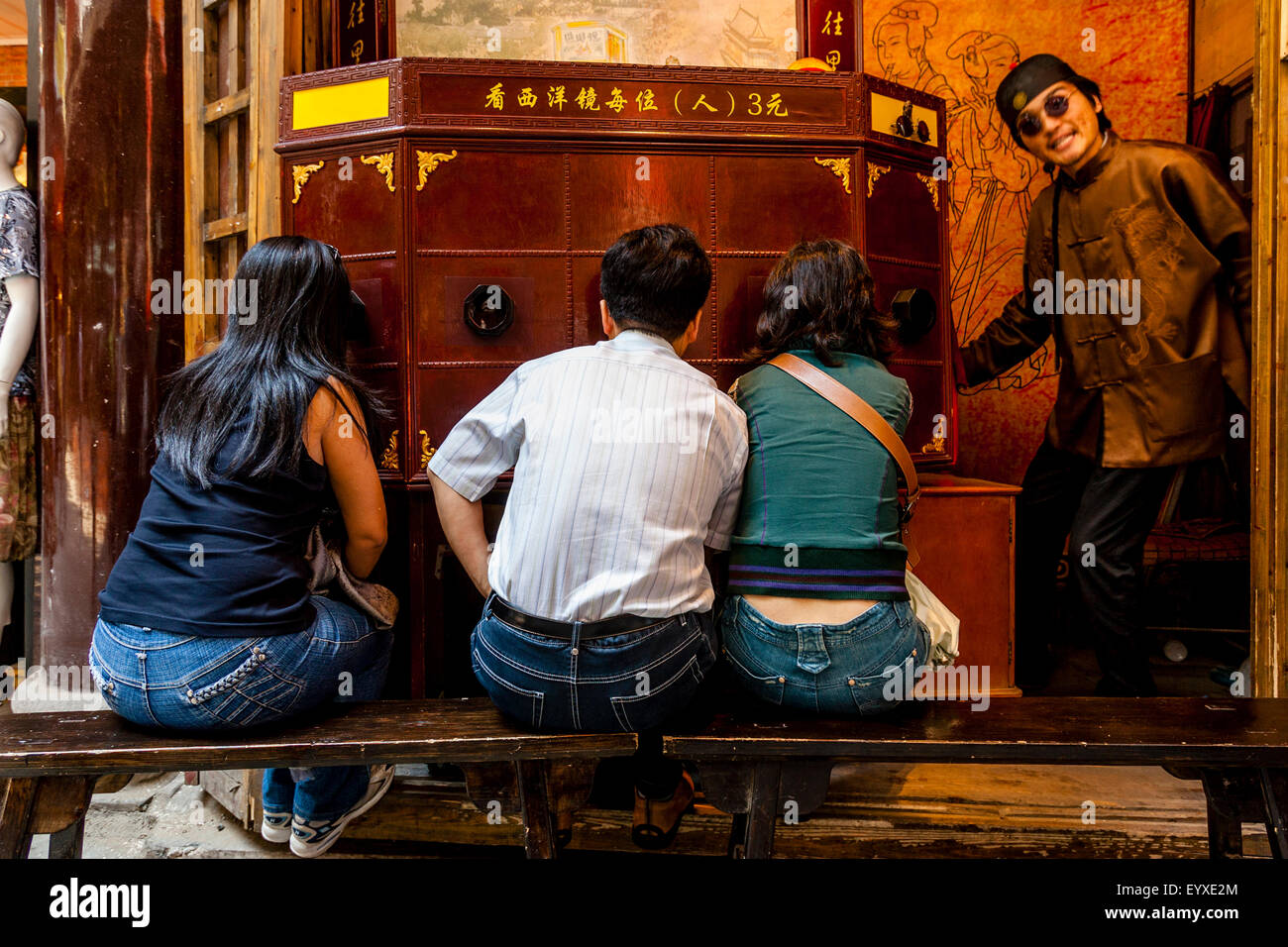 People Watch A Traditional Chinese Peep Show, Old Shanghai, Shanghai, China  - Stock