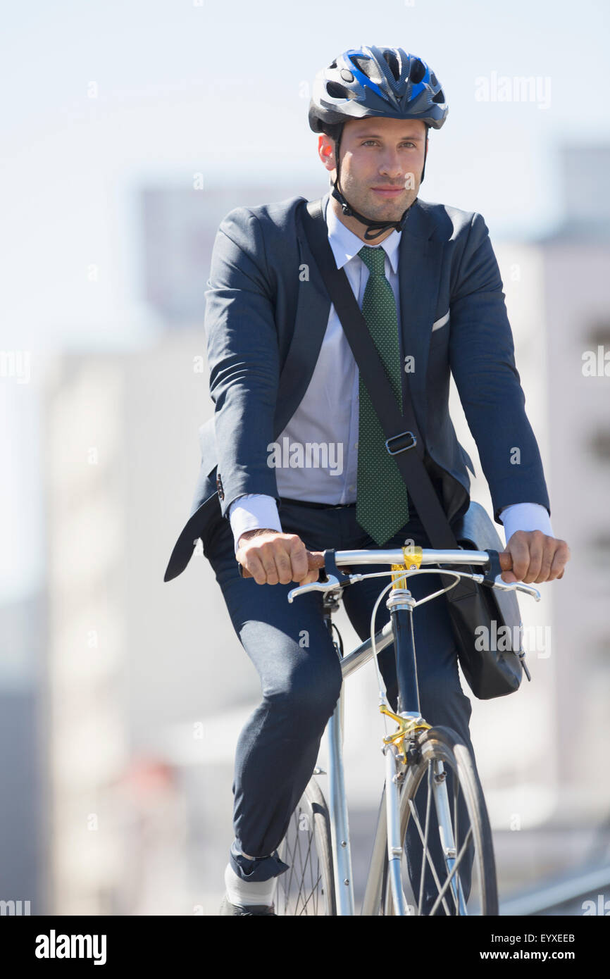 Businessman in suit commuting on bicycle with helmet - Stock Image