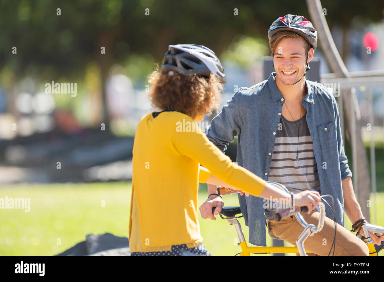 Man and woman with bicycles wearing helmets and talking in park Stock Photo