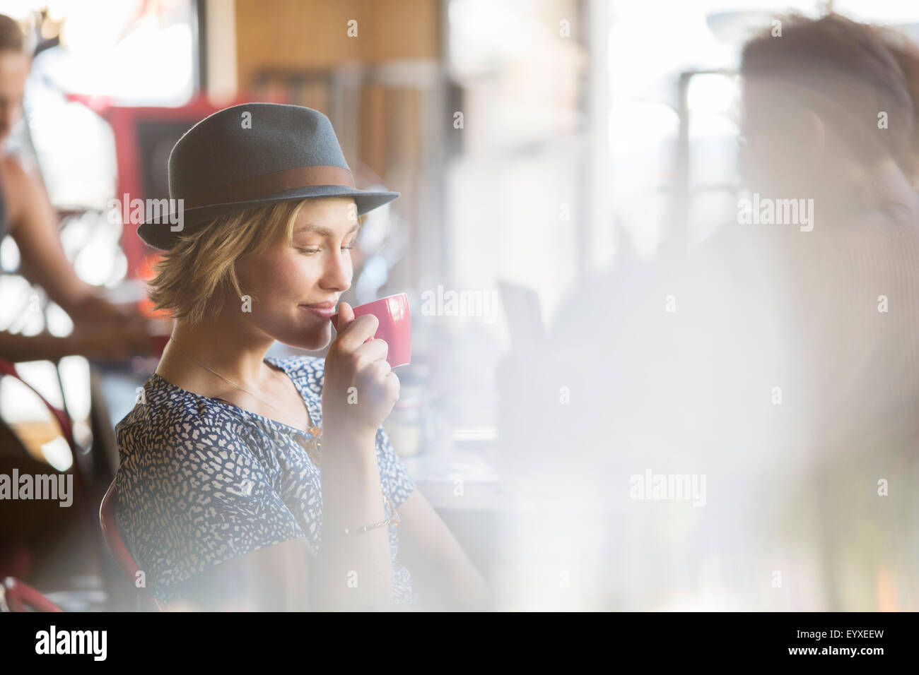Woman in hat drinking coffee in cafe - Stock Image