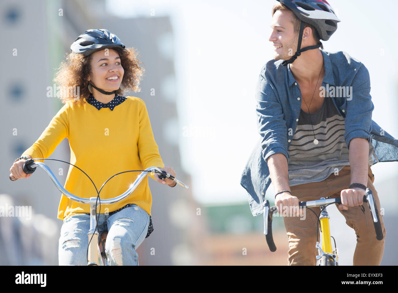 Young couple with helmets riding bicycles in city Stock Photo