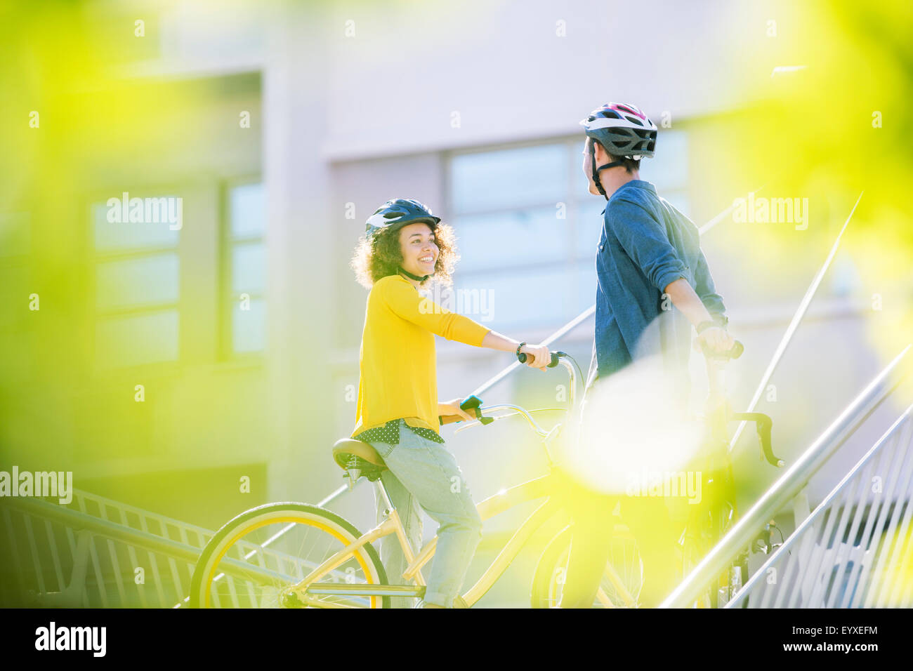 Man and woman with helmets on bicycles talking Stock Photo
