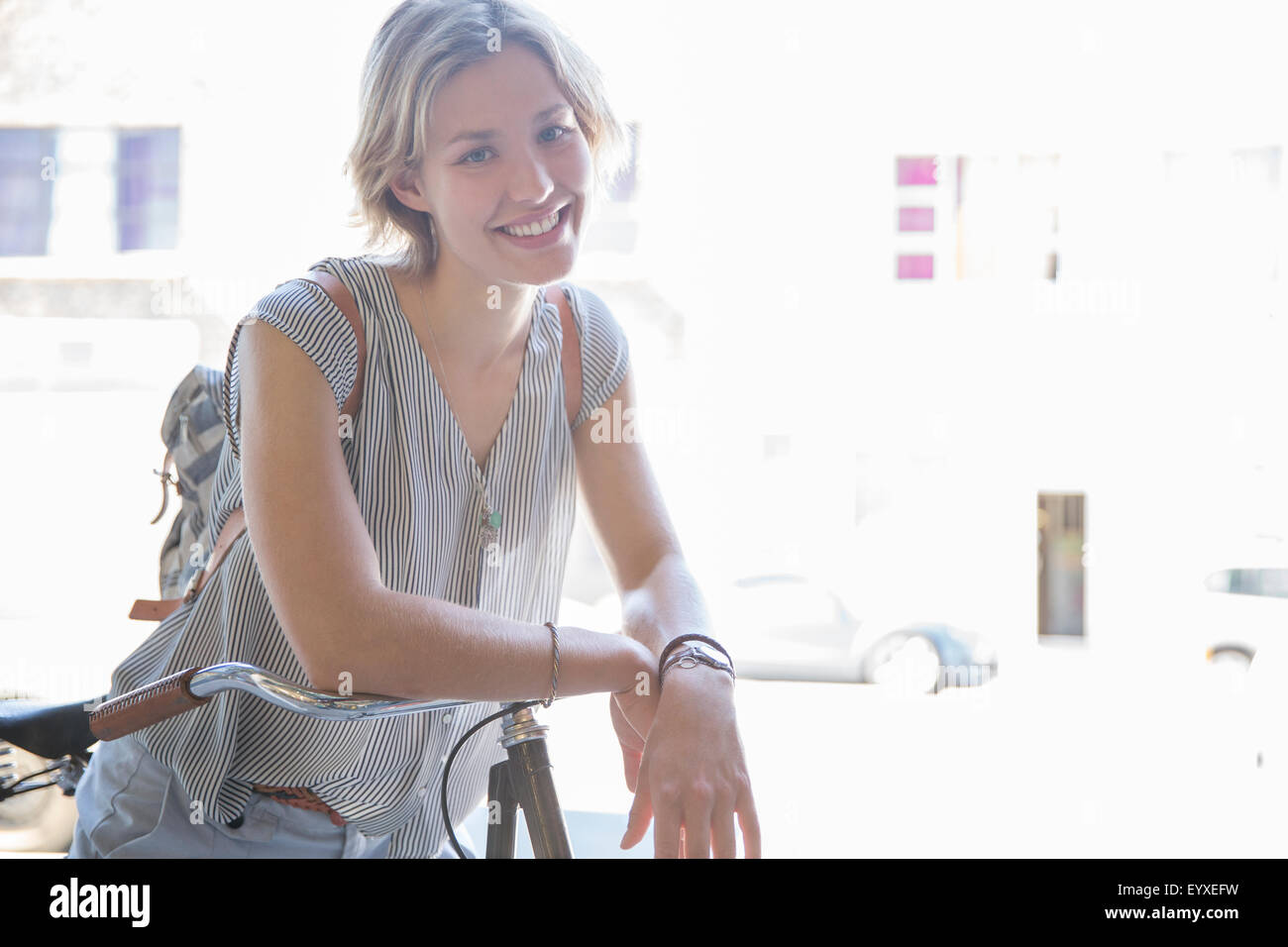 Portrait smiling woman on bicycle - Stock Image