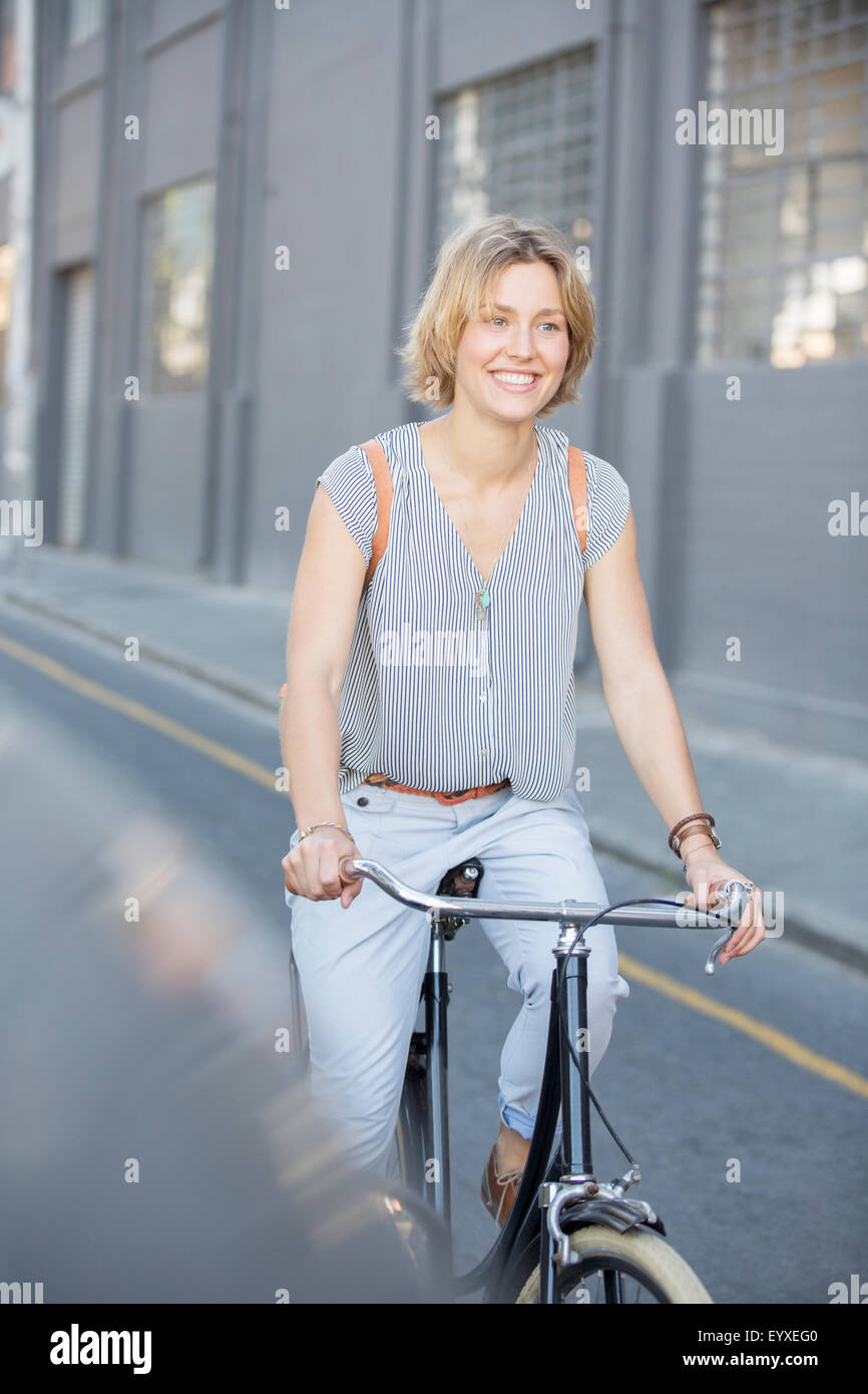 Smiling blonde woman riding bicycle on urban street - Stock Image