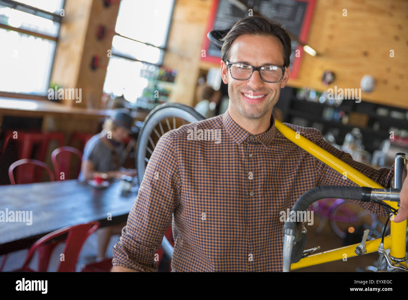 Portrait smiling man with eyeglasses carrying bicycle in cafe - Stock Image