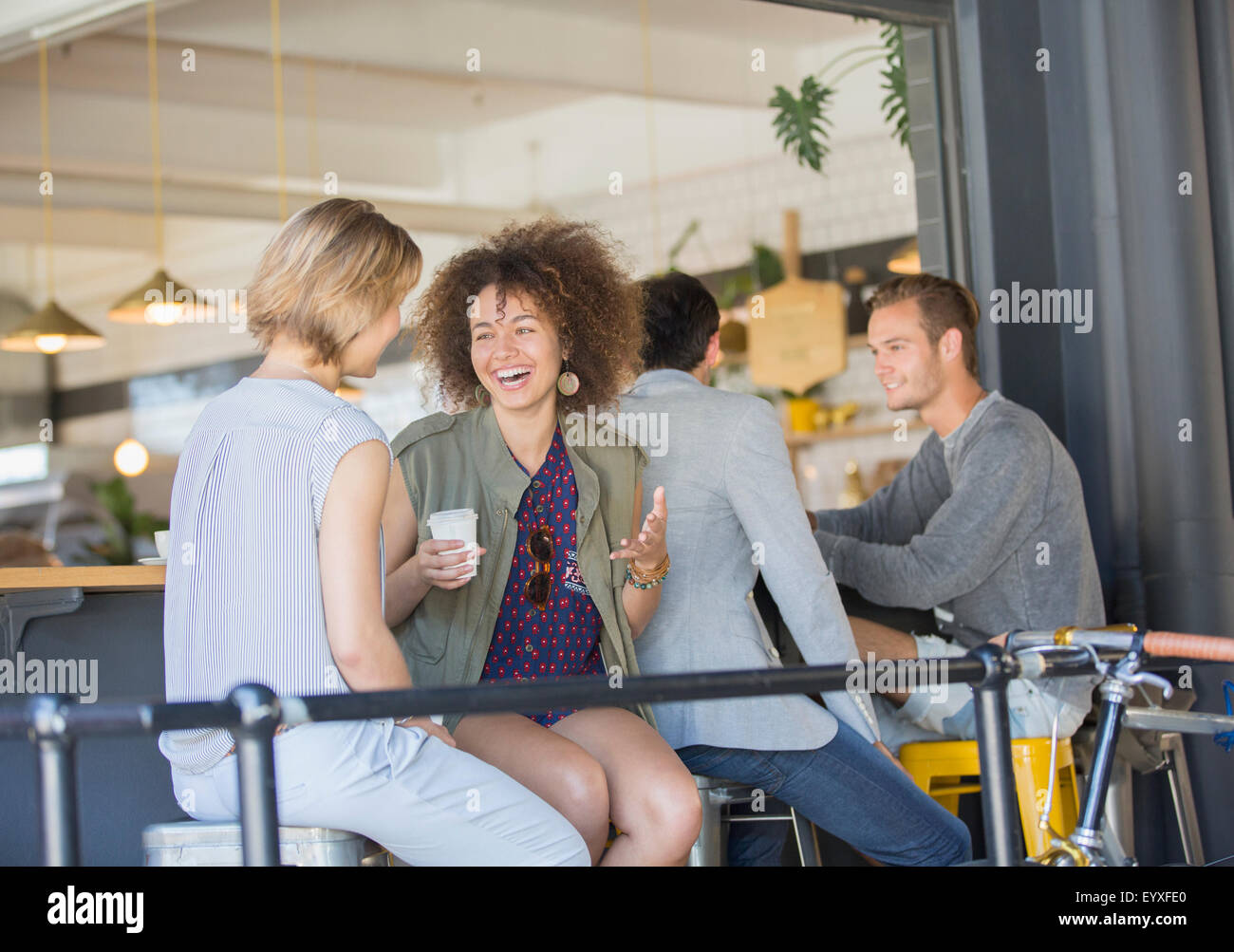 Laughing friends hanging out drinking coffee on cafe patio - Stock Image