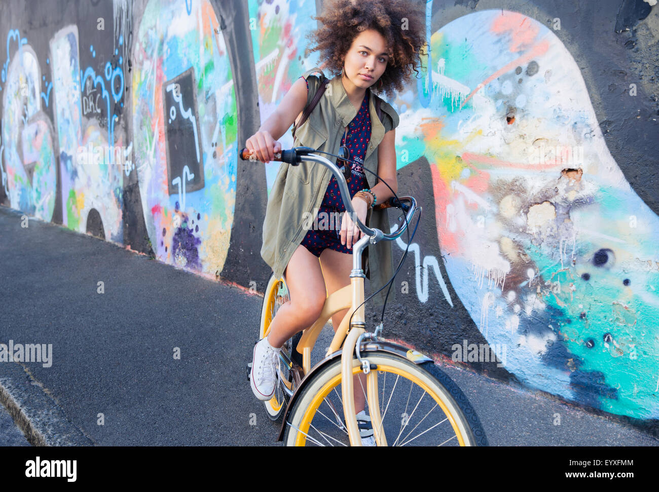 Portrait serious woman with afro on bicycle next to urban graffiti wall - Stock Image