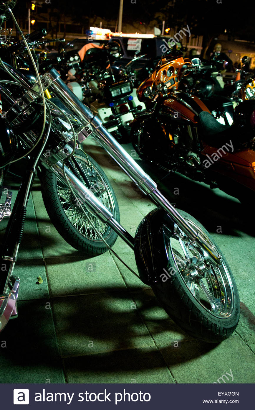 The long front chrome fork of a cruiser style road motorcycle gleams while casting a shadow of its wheel beneath. - Stock Image