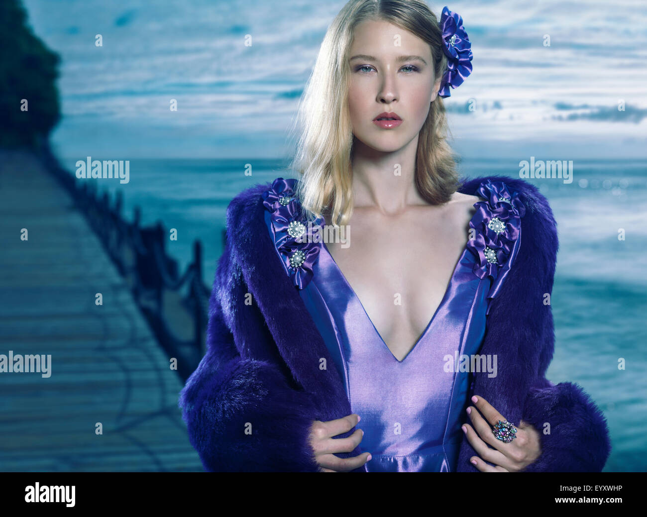 Beauty portrait of a young beautiful blond woman wearing a blue evening dress and a fur jacket outdoors at waterfront - Stock Image