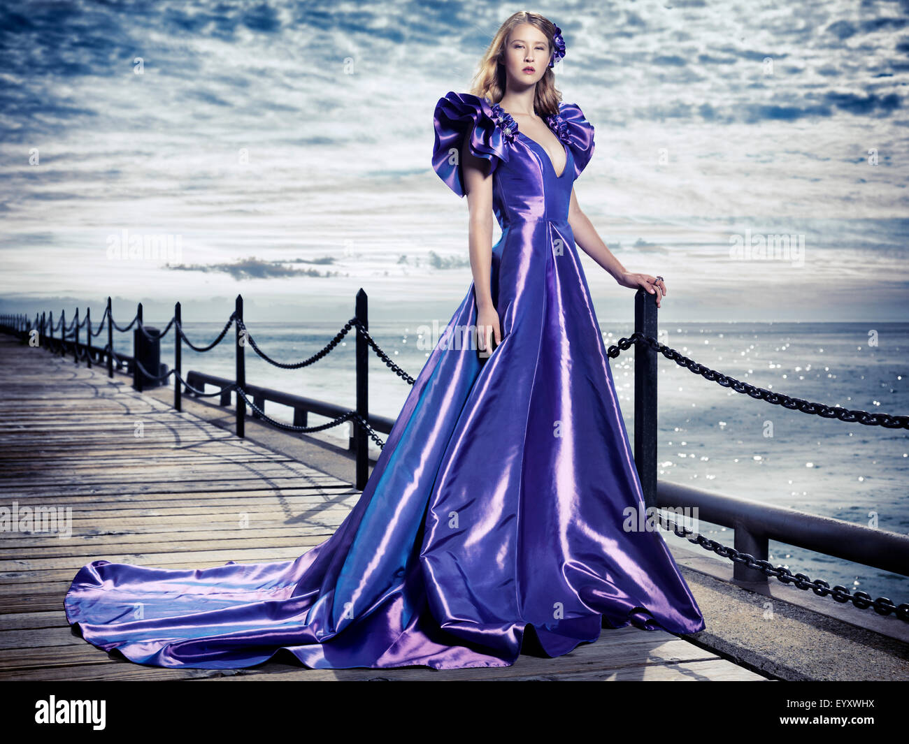 Young woman wearing a beautiful long blue evening gown standing at waterfront, artistic fashion portrait - Stock Image