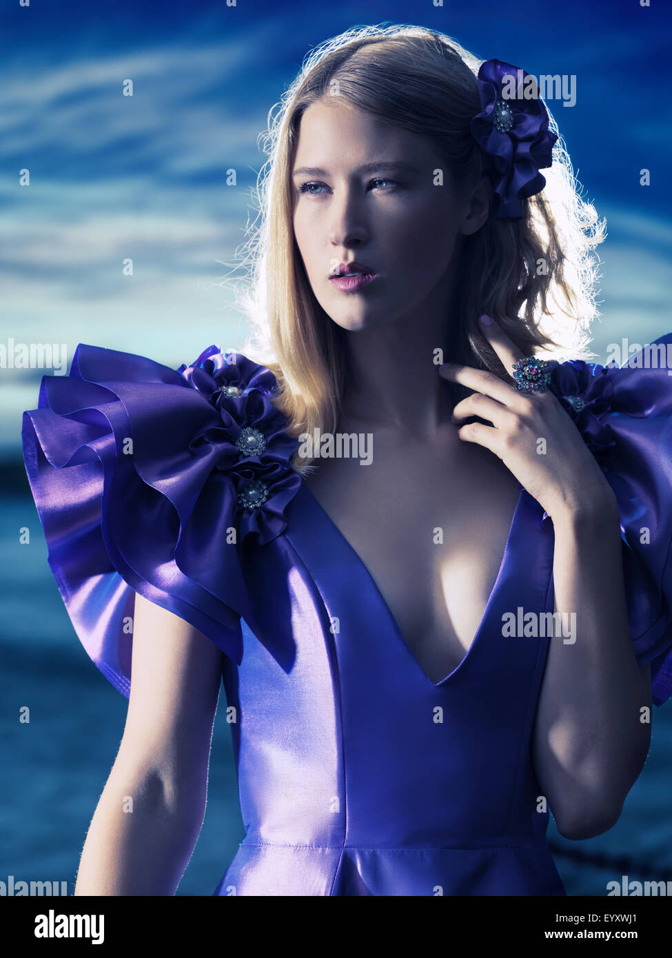 Beauty portrait of a young beautiful blond woman wearing a blue evening dress outdoors - Stock Image