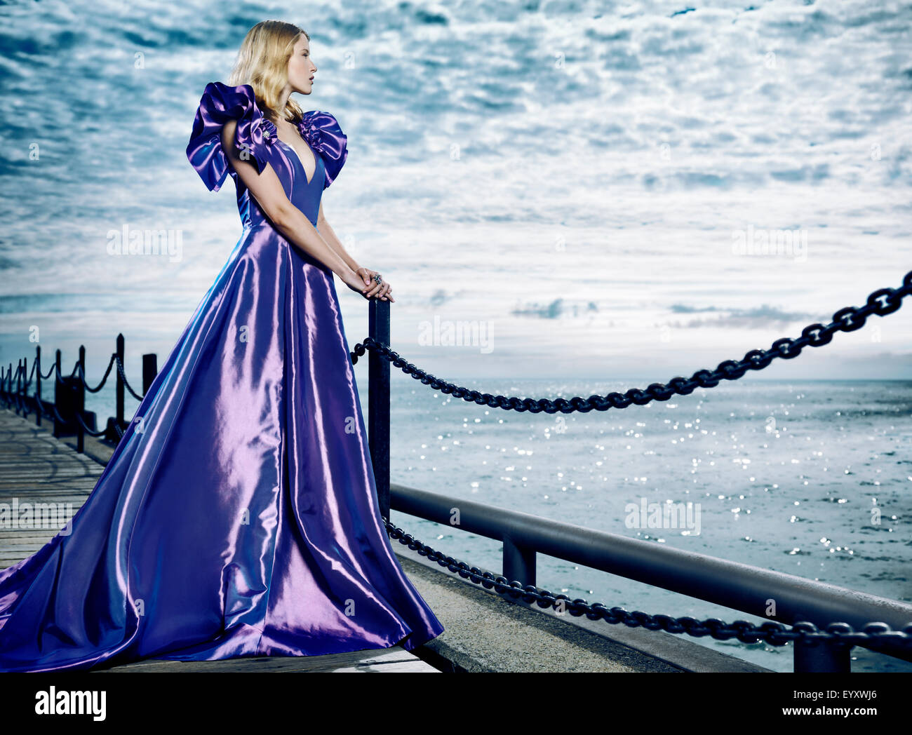 Young blond woman wearing a beautiful long blue dress, evening gown, standing at waterfront looking at the sea - Stock Image