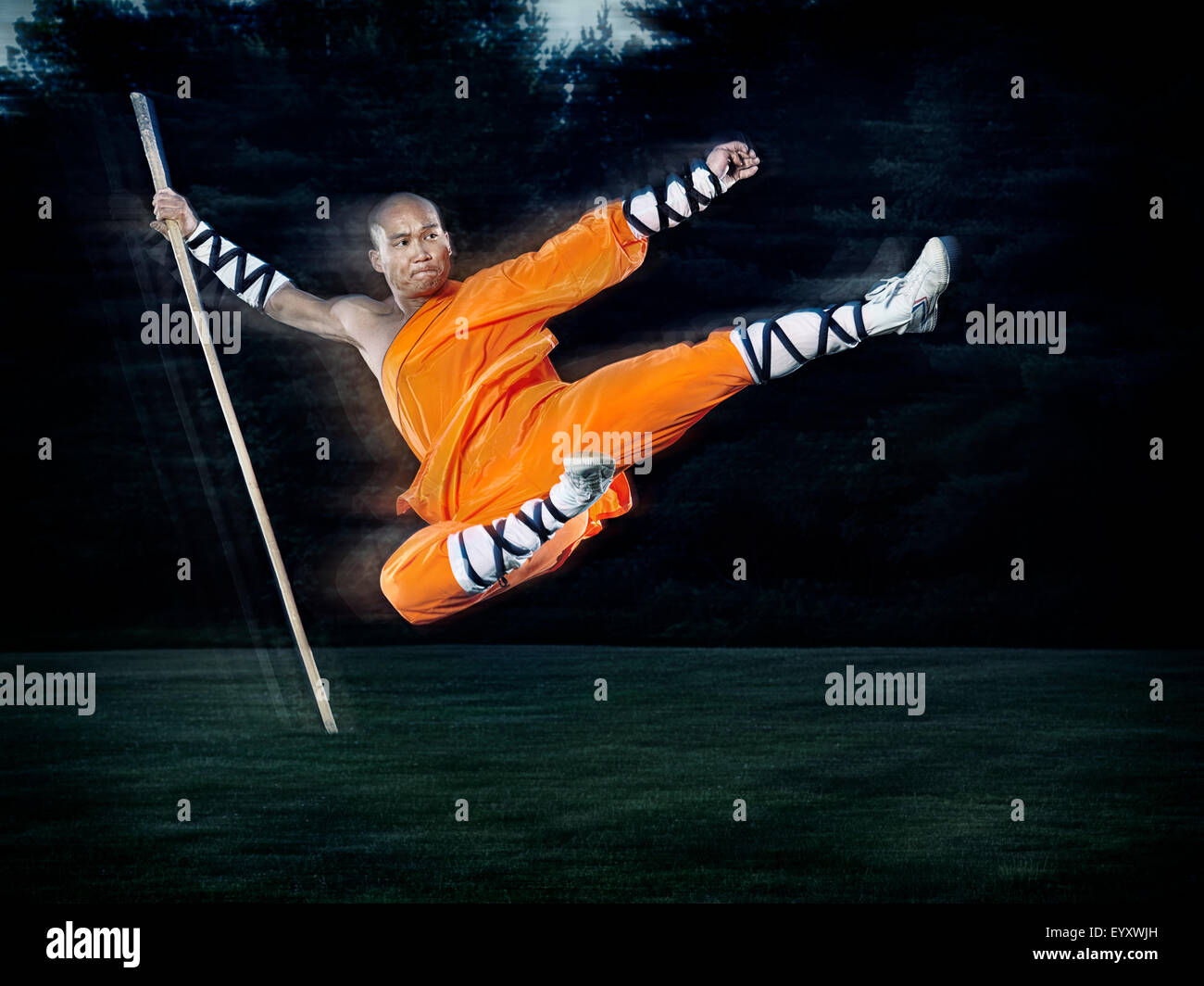Shaolin warrior monk in mid-air flying kick jump with a staff outdoors - Stock Image