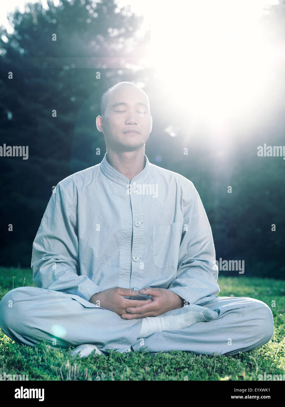 Shaolin monk meditating outdoors during sunrise in sunlight - Stock Image