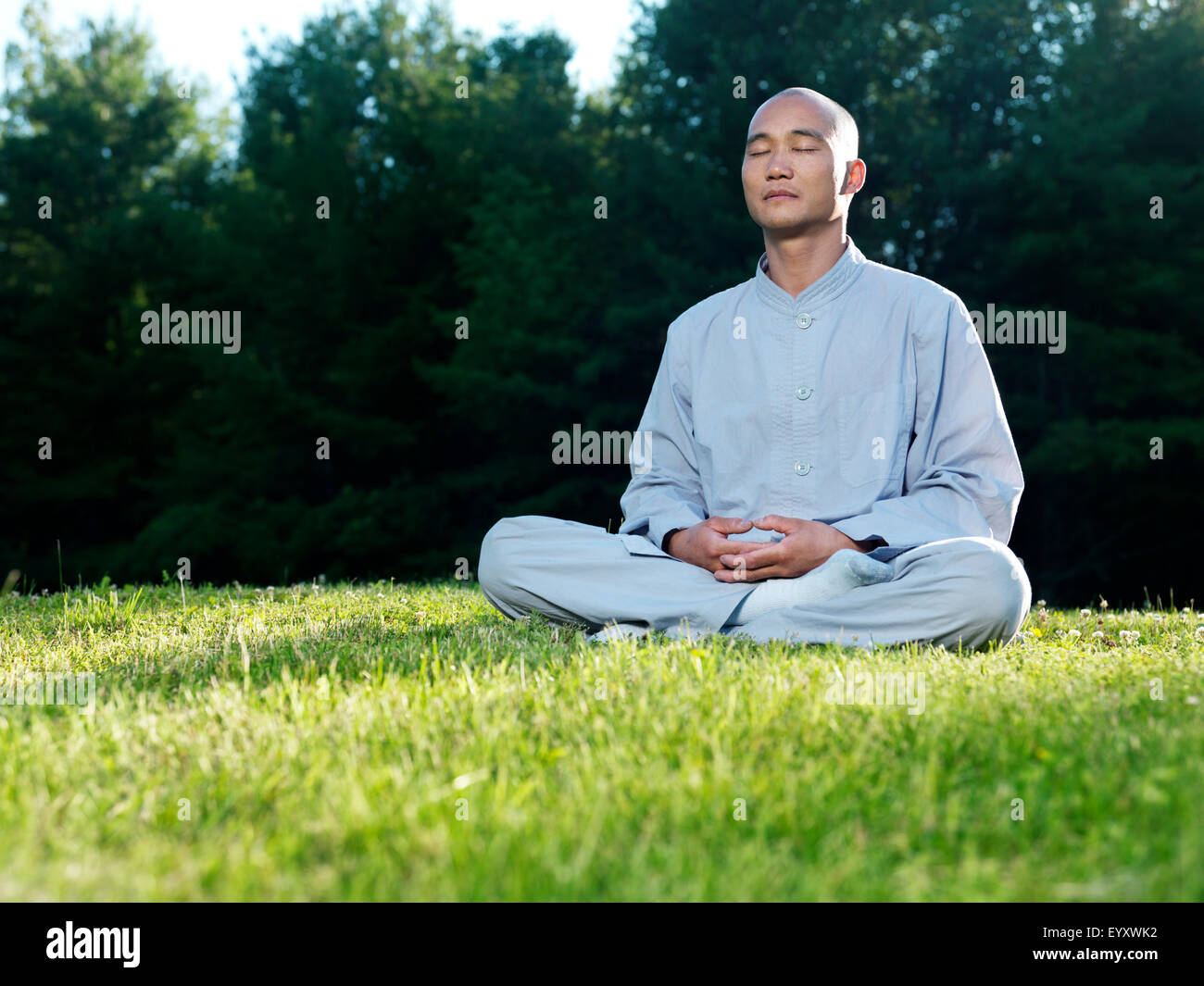Shaolin monk meditating outdoors during sunrise sitting on green grass - Stock Image