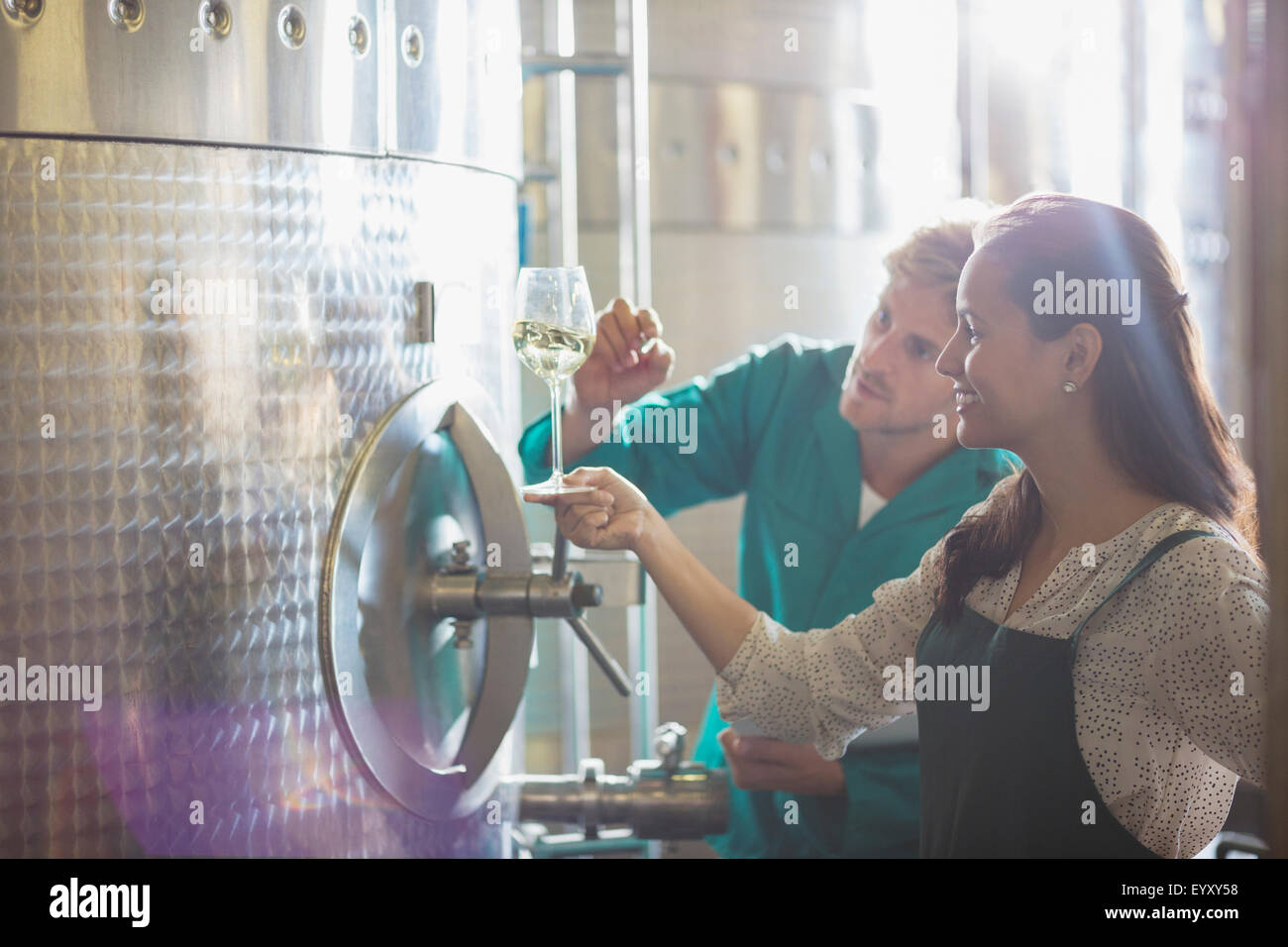 Vintners examining white wine at stainless steel vat in winery cellar - Stock Image