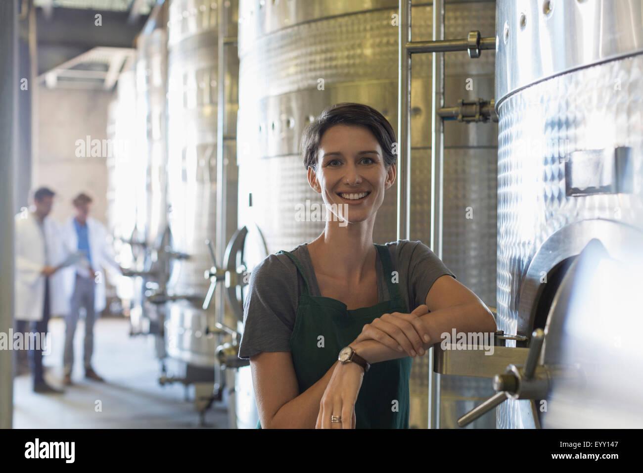Portrait smiling vintner at stainless steel vat in winery cellar - Stock Image