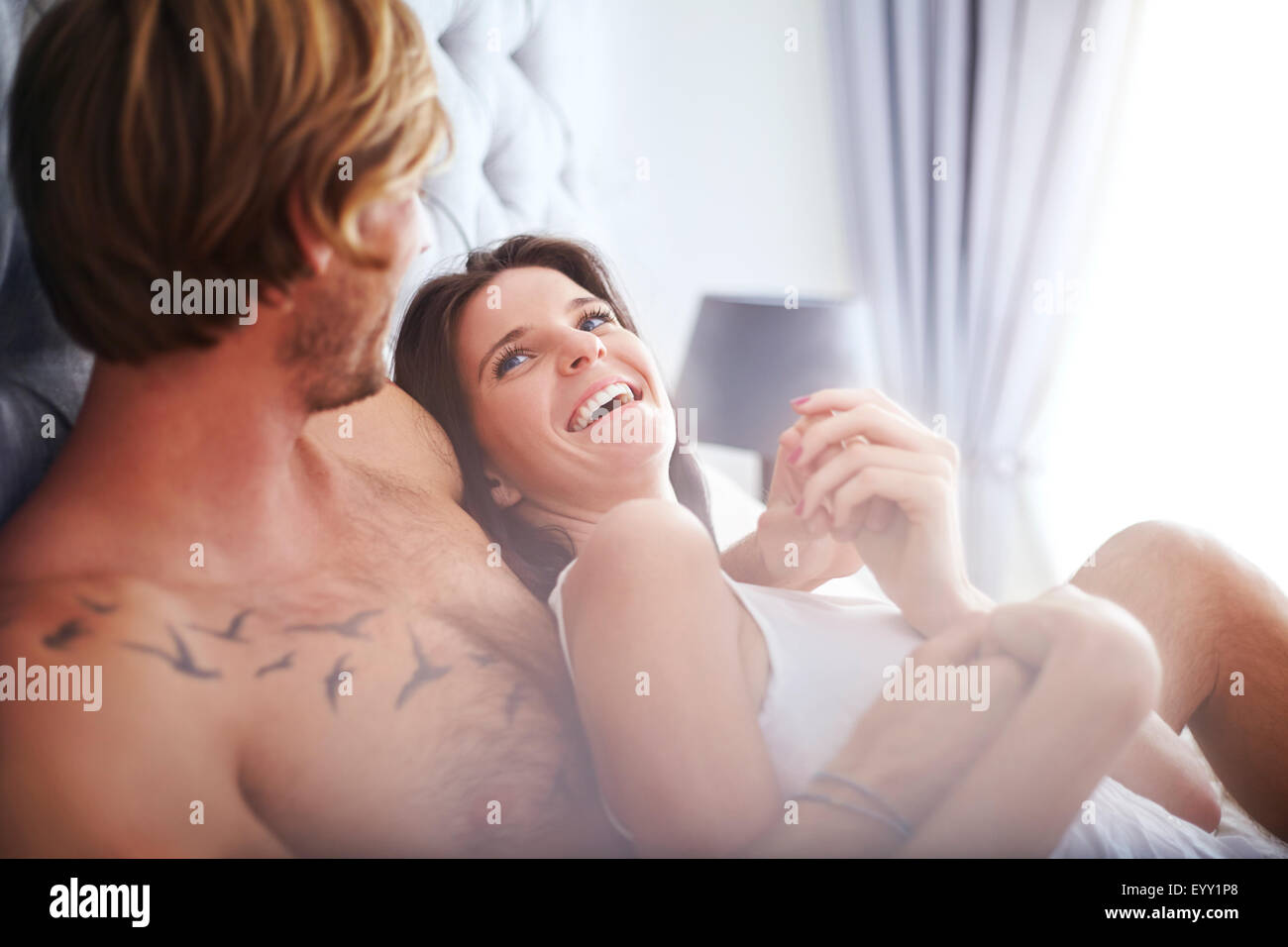 Casual couple cuddling on bed - Stock Image