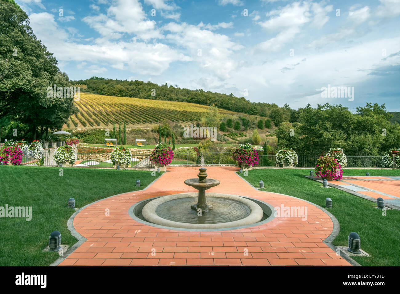 Fountain and walkway in landscaped grounds over rural fields, Radda in Chianti, Siena, Italy - Stock Image