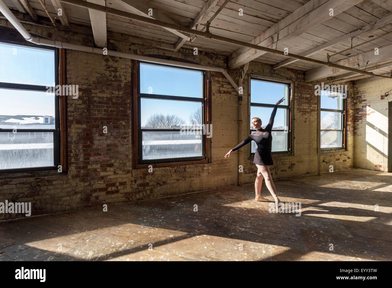 Caucasian ballet dancer performing in sunny loft - Stock Image