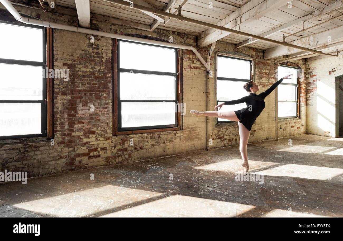 Caucasian ballet dancer performing in sunny loft room - Stock Image