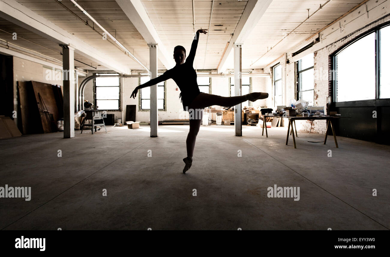 Caucasian ballet dancer performing in loft - Stock Image