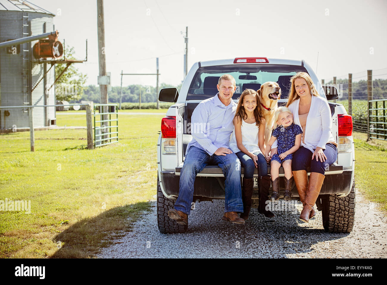 Caucasian family and dog sitting in truck bed on farm Stock Photo