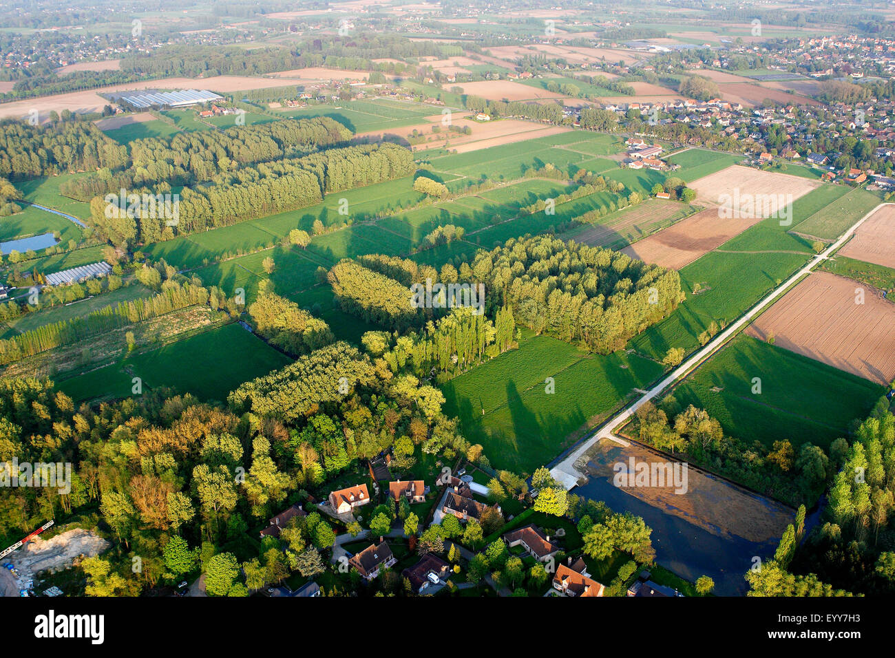 urbanisation at the border of agricultural area with fields, grasslands and hedges from the air, Belgium - Stock Image
