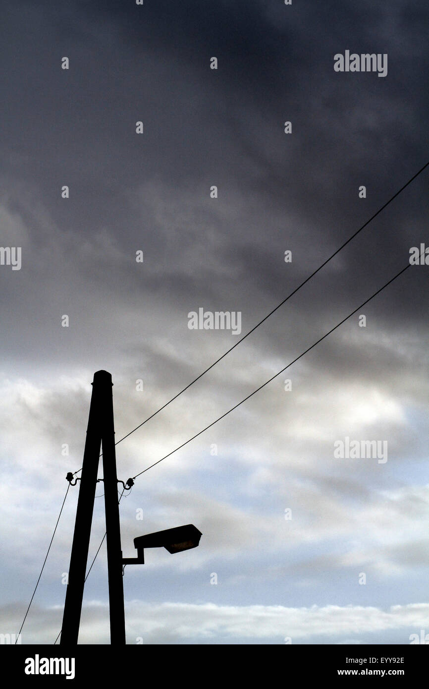 dark rain cloud above street lighting and overhead power lines, Germany - Stock Image
