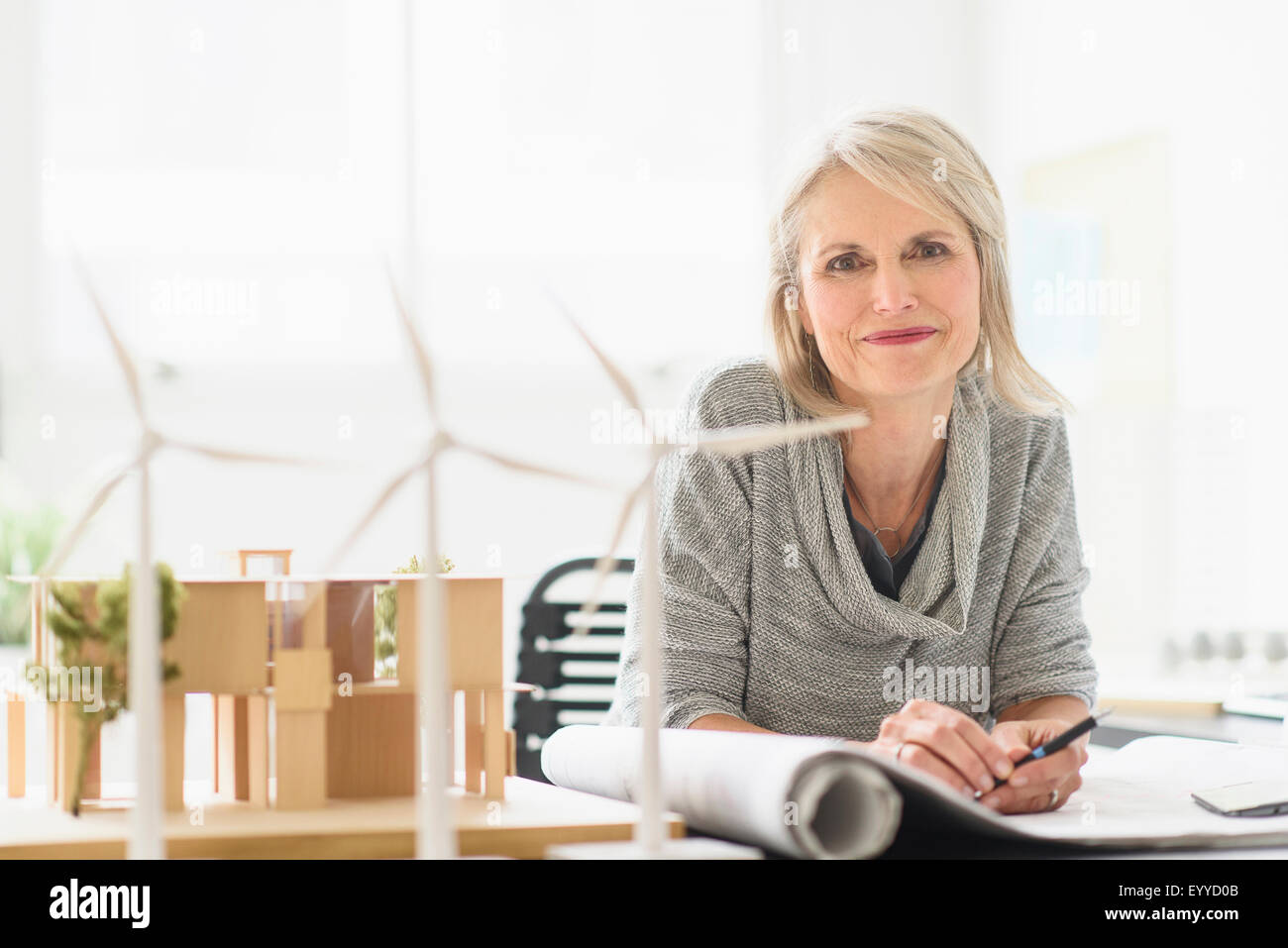 Older Caucasian architect sitting in office Stock Photo