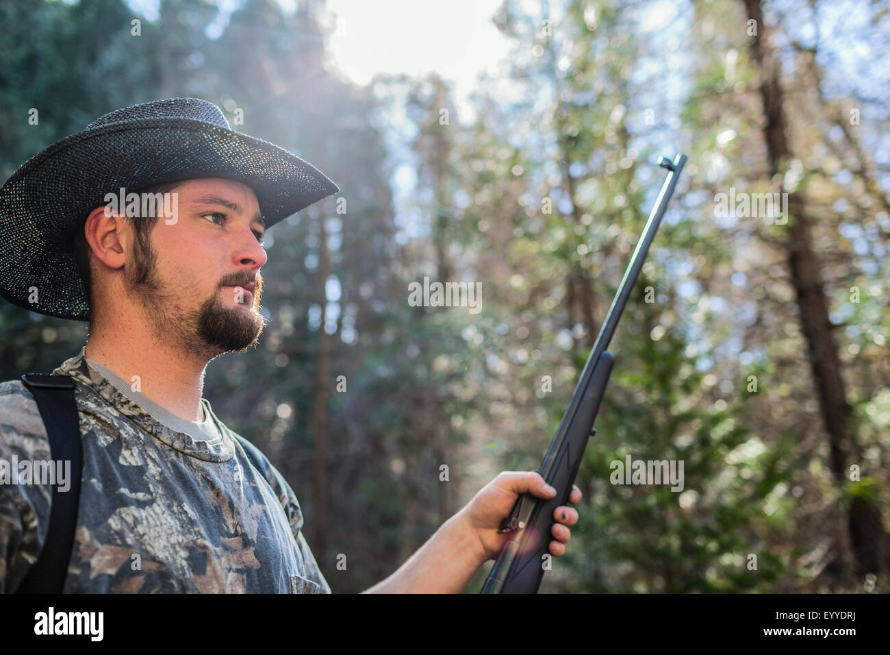 Caucasian hunter holding gun in forest Stock Photo