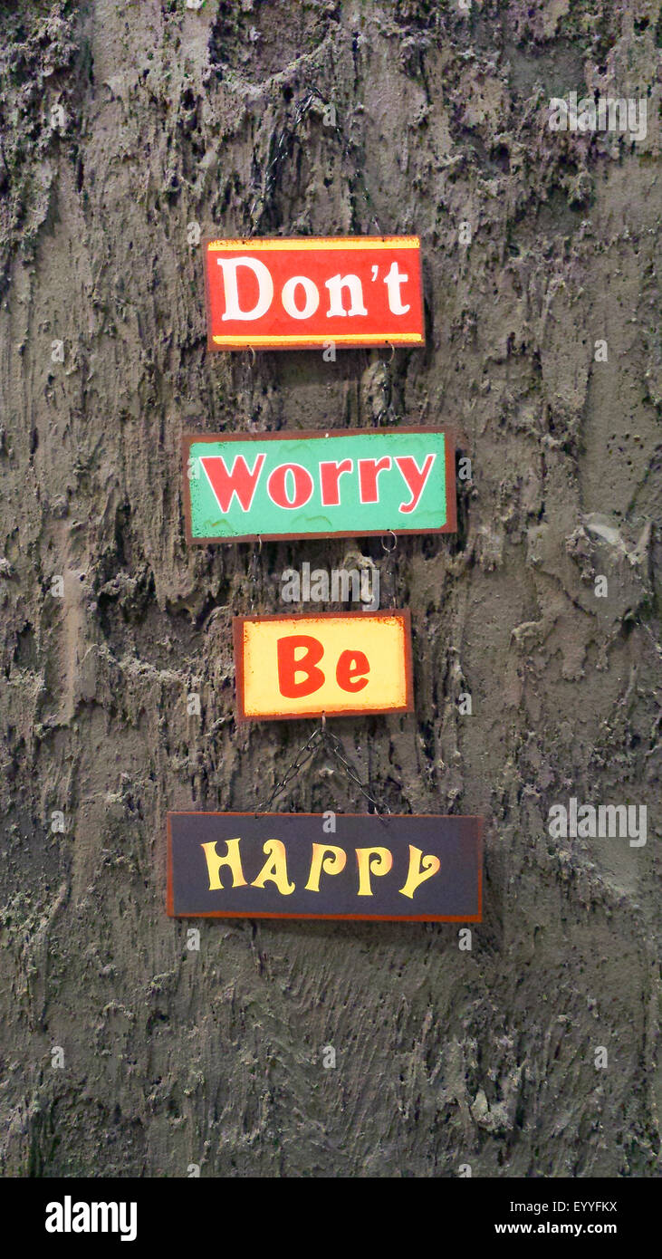Don't worry be happy' signs at a wall - Stock Image