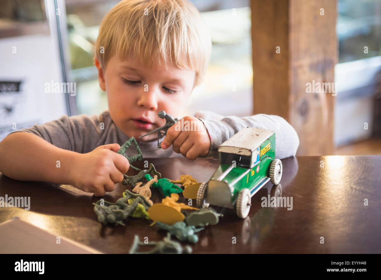 Caucasian boy playing with toys on table - Stock Photo