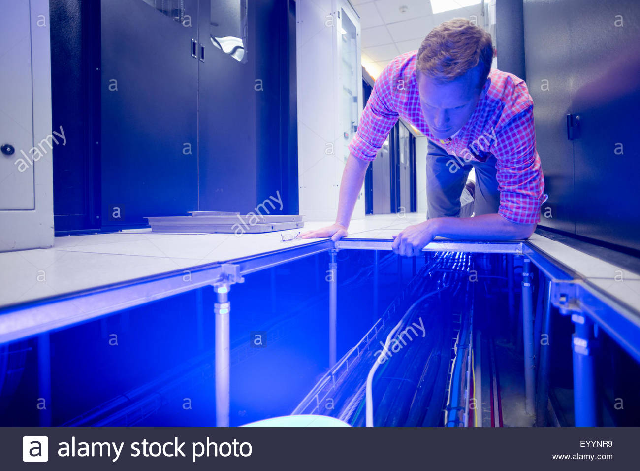 Technician checking cabling under floor of data centre server room - Stock Image