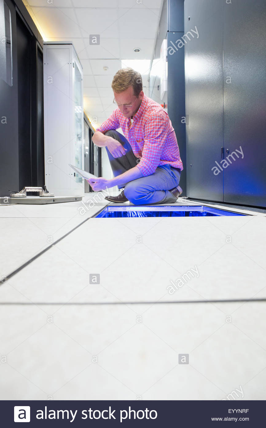 Technician with digital tablet checking cabling under floor of data centre server room - Stock Image