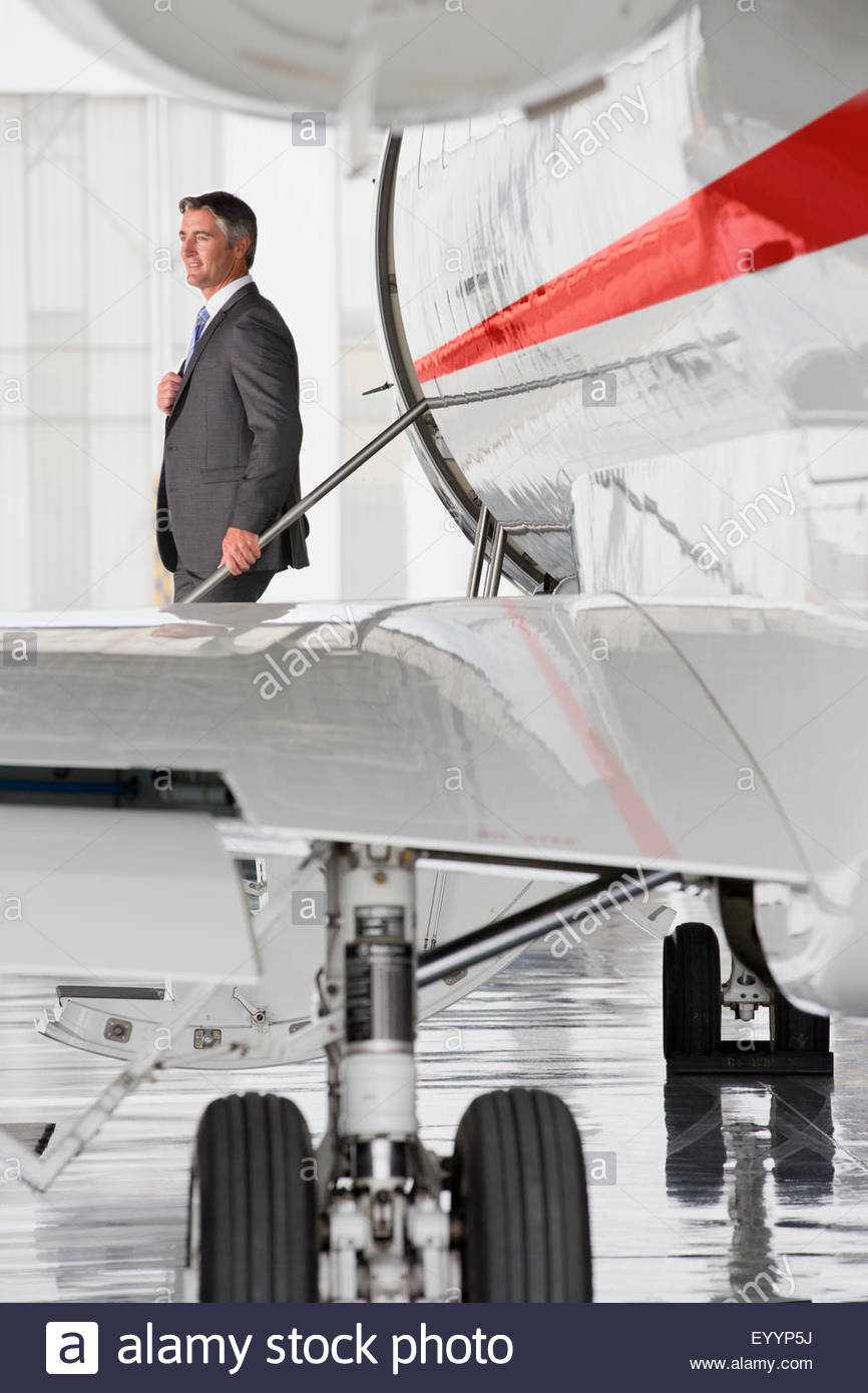 Businessman exiting on stairs of private jet - Stock Image