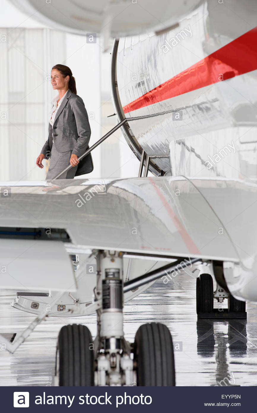 Businesswoman exiting on stairs of private jet - Stock Image