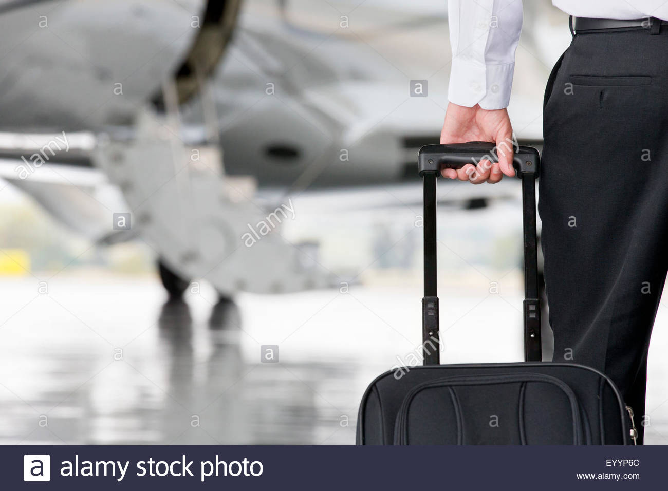 Businessman pulling carry-on suitcase towards private jet - Stock Image