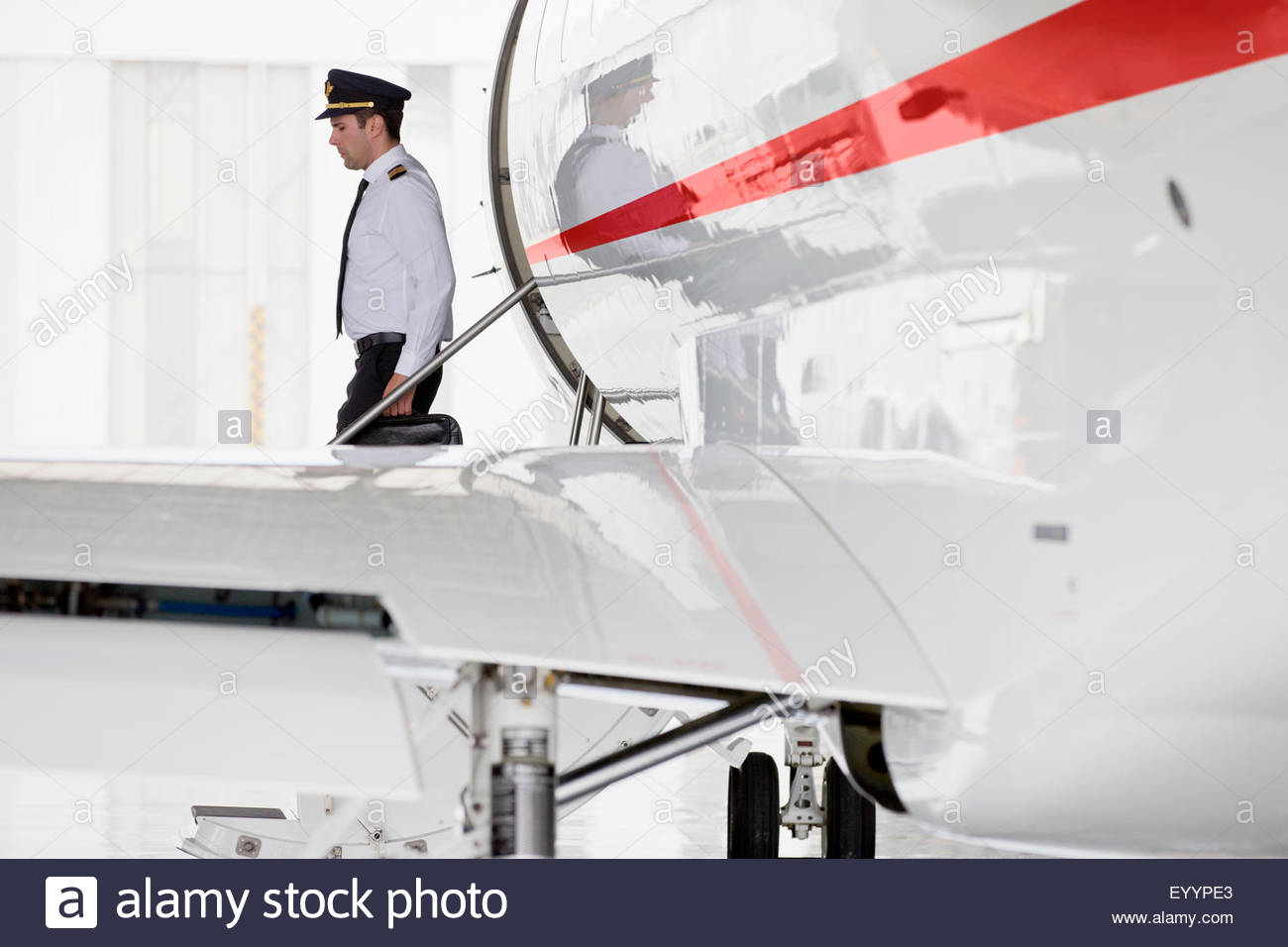 Pilot exiting private jet - Stock Image