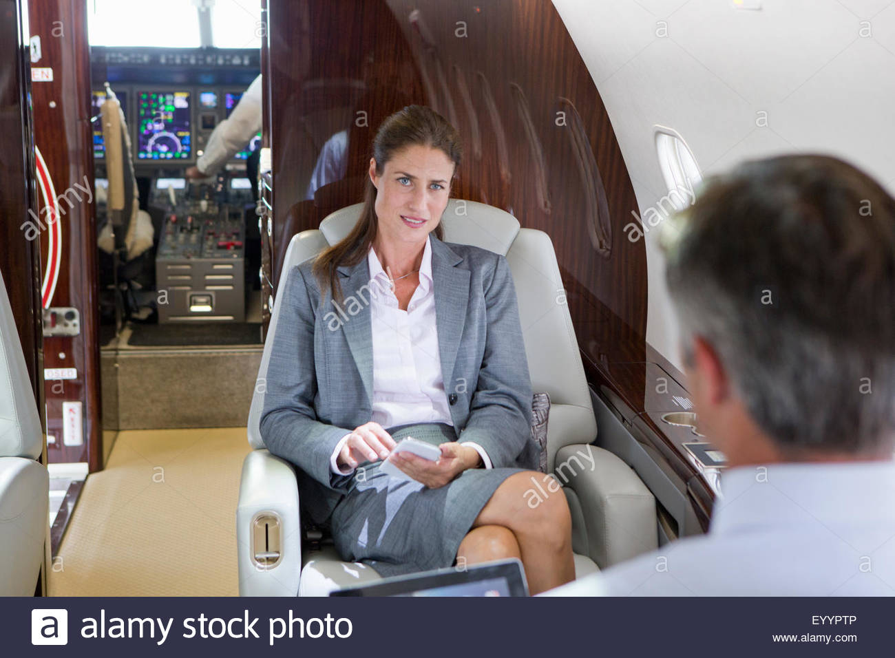 Businesswoman with phone and Businessman with digital tablet having meeting on private jet - Stock Image