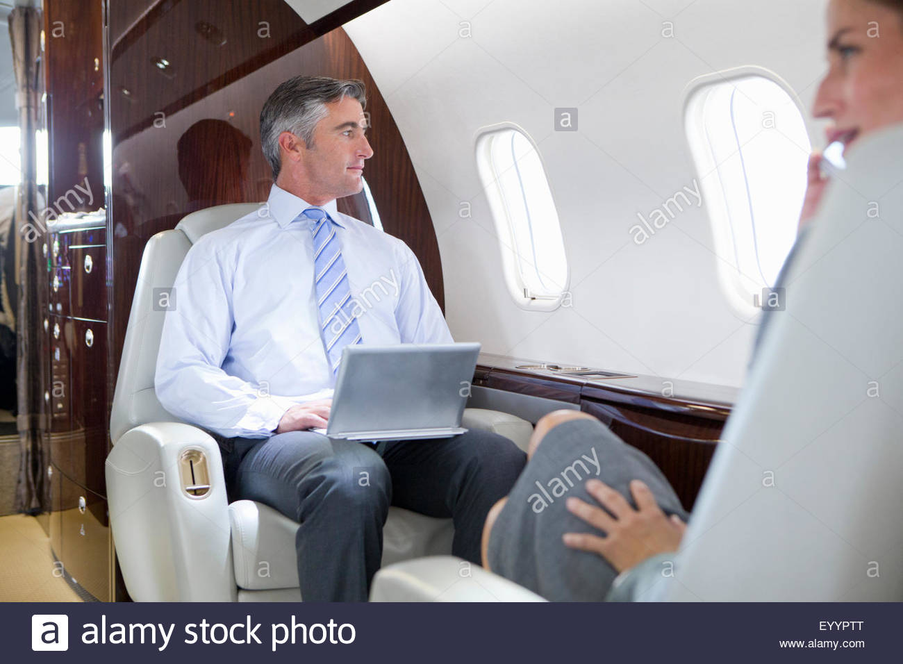 Businesswoman on phone and Businessman with digital tablet having meeting on private jet - Stock Image