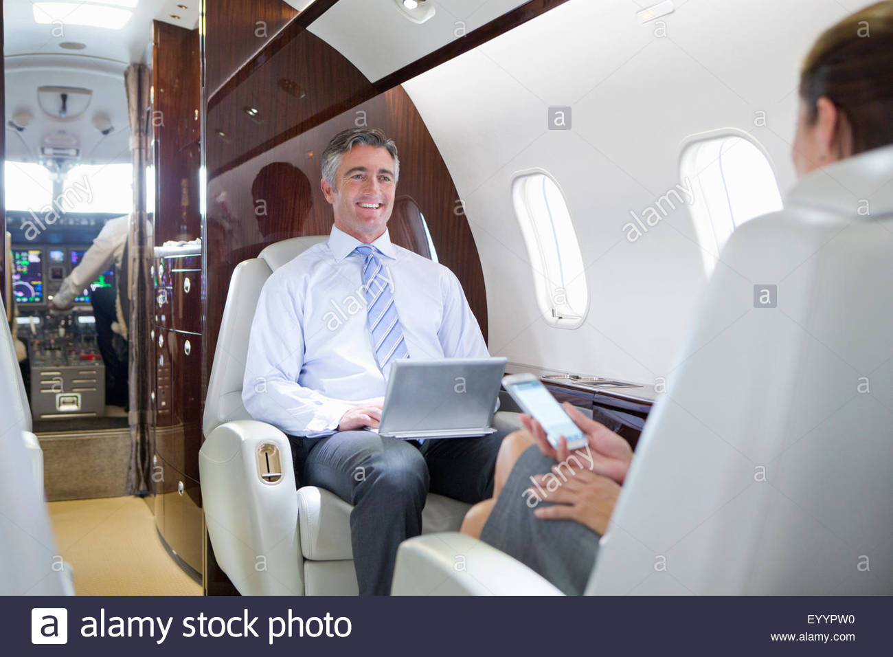 Businesswoman on phone and smiling Businessman with digital tablet having meeting on private jet - Stock Image