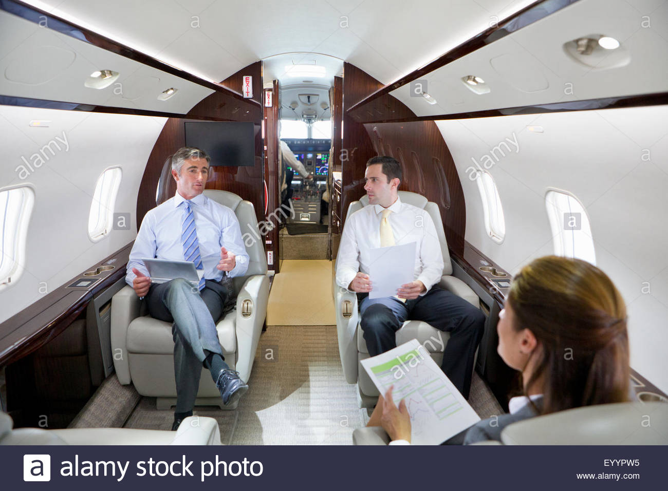 Businesswoman and Businessmen with digital tablet having meeting on private jet - Stock Image